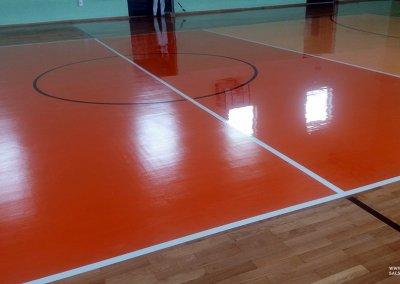 Podczas lakierowania ostatniej warstwy lakieru na sali sportowej.